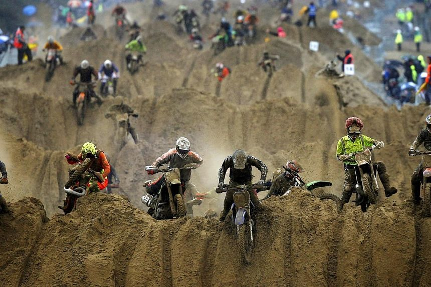 Riders crest a dune during the opening lap of the main race of the 2013 RHL Weston beach race, an offshoot of enduro and motocross racing, in Weston-Super-Mare, south-west England. -- PHOTO: AFP