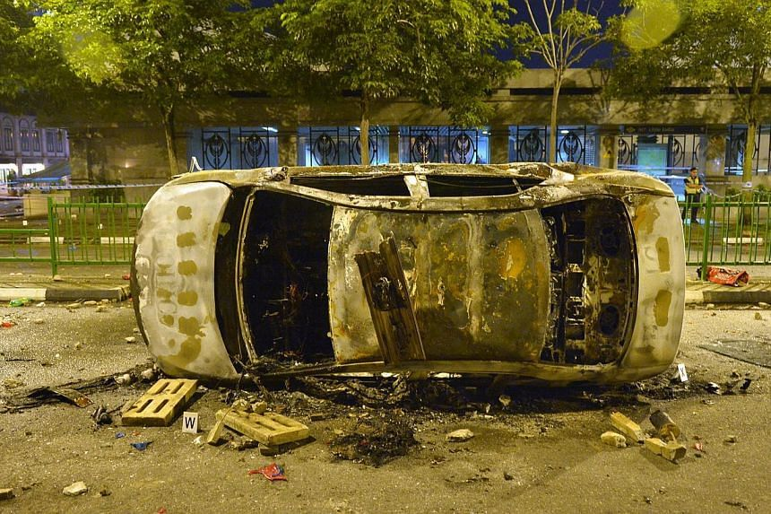 A wrecked police car is pictured on Dec 9, 2013. The repatriation of 53 migrant workers involved in the Dec 8 riot in Little India has begun. -- ST FILE PHOTO: ALPHONSUS CHERN