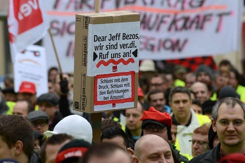 """Employees of internet retail giant Amazon hold up posters reading """"Dear Jeff Bezos, we are verdi - Call us - Stop the pressure, the short term contracts at Amazon"""" as they stage a strike in front of the company's logistics center in Bad Hersfeld, cen"""