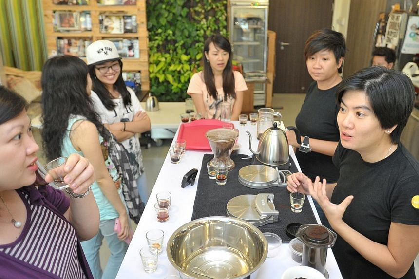 Ms Pamela Chng (right), founder of Bettr Barista Coffee Academy, with her students during a brewing demonstration. Three organisations won the 2013 President's Challenge Social Enterprise Award on Friday, Dec 20, 2013. -- ST FILE PHOTO: LIM YAOHUI
