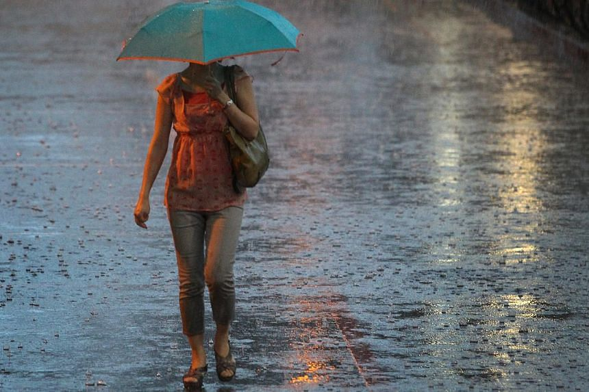 A woman walks in the rain with an umbrella outside Boon Lay MRT station on Dec 13, 2013.Heavy rain and moderate to rough sea conditions are expected to lash Singapore between now and Sunday. -- ST PHOTO: JASON QUAH