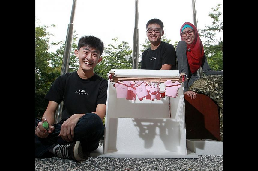 SUTD freshmen (from left) Tan Chang Tat, 21, Benjamin Hoong, 20, and Faizah Ja'affar, 20, with their prototype of SmartDry, a clothes-drying rack that retracts the laundry on detecting rain.