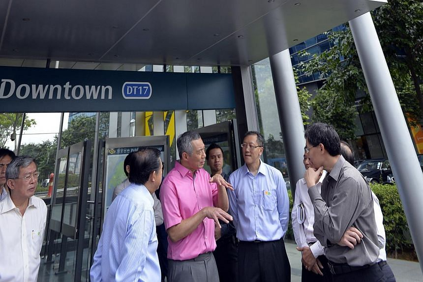 Prime Minister Lee Hsien Loong outside the new Marina Bay Downstown station on Dec 21, 2013. With him are (from right) Transport Minister Lui Tuck Yew, Land Transport Authority (LTA) deputy chief executive of infrastructure and development Chua Chong