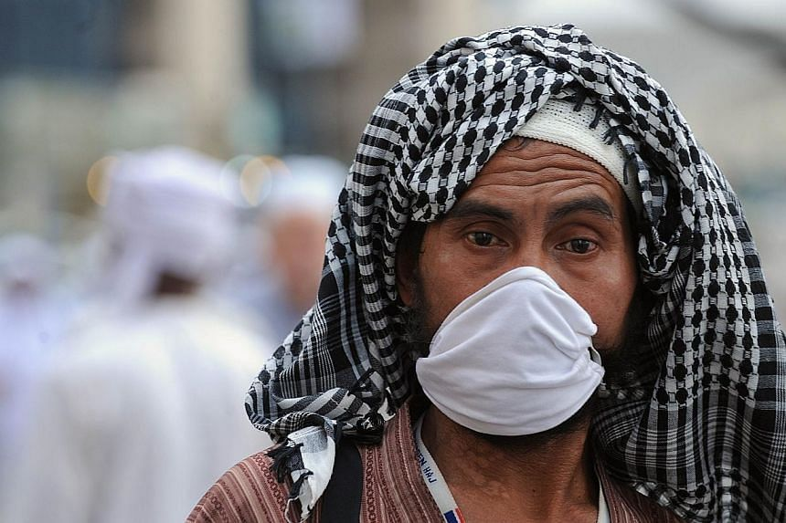 A Muslim pilgrim wears a mask as he arrives to perform evening prayers in Mecca's Grand Mosque, on Oct 8, 2013, prior to the start of the annual hajj pilgrimage on Oct 13.The Saudi health ministry announced on Saturday a new MERS death, raising