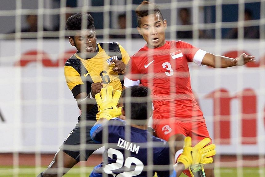 Sahail Suhaimi (right), attempting to kick the ball into the net while watched by goalkeeper Abu Bakar Mohd Farhan and Deandrn Saarvindran (left). Singapore beat Malaysia 2-1 to win the bronze medal match of the 27th SEA Games in Naypyitaw, Myanmar,&