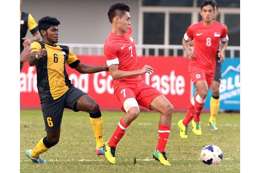 Gabriel Quak (right) and Deandrn Saarvindran (left) go for the ball. Singapore beat Malaysia 2-1 to win the bronze medal match of the 27th SEA Games in Naypyitaw, Myanmar, on Saturday, Dec 21, 2013. -- ST PHOTO: LIM SIN THAI