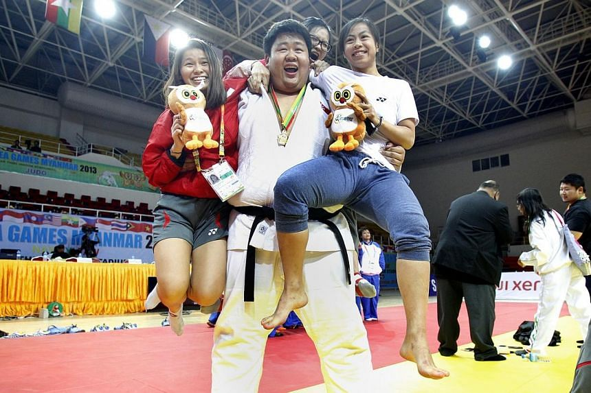 Singapore's Ho Han Boon is jumped onto by teammates (from left) Vanessa Ng, Ngo Yee Ling and Ang Xuan Yi after winning the gold medal in men's judo +100kg category during the 27th SEA Games in Naypyidaw's Zayar Thiri Indoor Stadium, Myanmar, on Satur