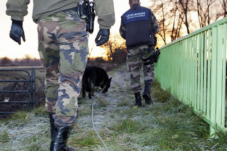 Gendarmes walk along the Dordogne river on Dec 21, 2013, in Lugon-et-l'Ile-du-Carnay, south-western France, after a helicopter carrying Chinese tycoon Lam Kok overflying his newly-purchased vineyard went down.There was little hope of finding al