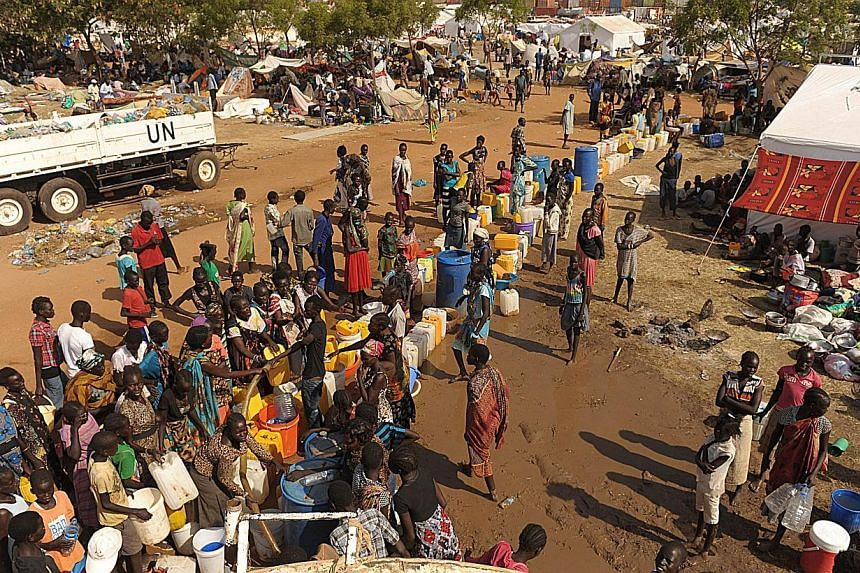 South Sudanese women queue for water being distributed from a UN resevoir at the United Nations Mission in South Sudan (UNMISS) compound in Juba on December 21, 2013 where tension remains high fueling an exodus of both local and foreign residents fro