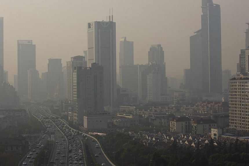 Buildings and cars are seen in the haze in downtown Shanghai, on Dec 2, 2013. Another Chinese city has capped the total number of car licence plates it will issue annually, state media said on Sunday, following moves by Beijing and other metropo