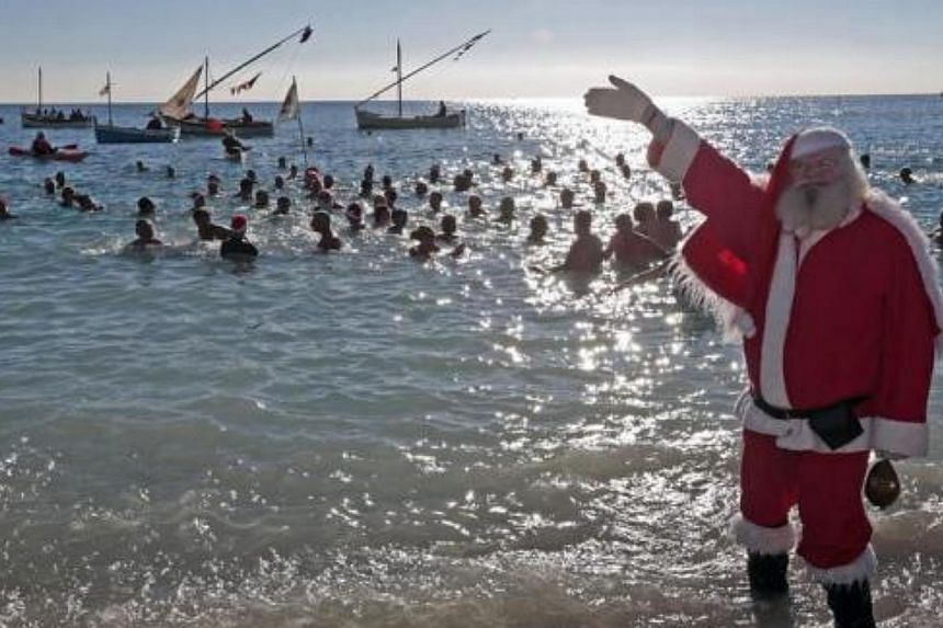 A man dressed as a Santa Claus waves as he takes part in the traditional Christmas bath in Nice, south-eastern France, on Dec 15, 2013. -- FILE PHOTO: REUTERS