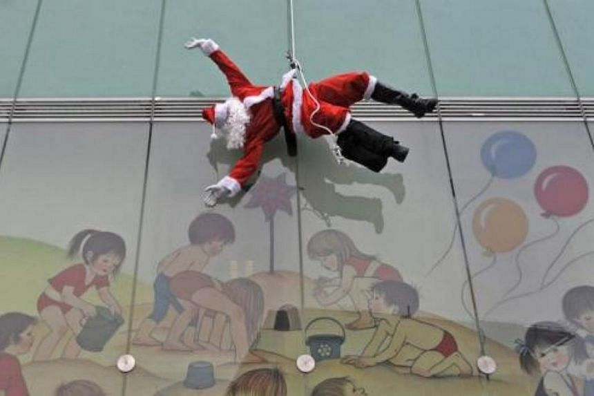 A member of the special police force dressed in a Santa suit descends from the roof of a paediatric clinic in Ljubljana, as part of a Christmas performance for patients of the clinic, on Dec 18, 2013.-- FILE PHOTO: REUTERS