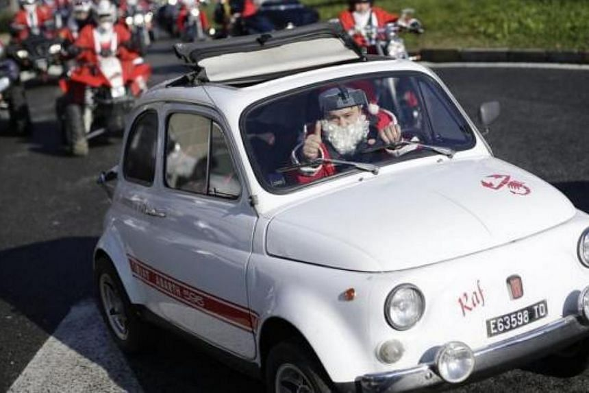 A man dressed as Santa Claus drives his Fiat 500 during a charity event to support children at Regina Margherita hospital in Turin, on Dec 1, 2013.-- FILE PHOTO: REUTERS