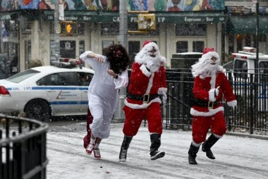 Revellers dressed as Santa Claus run in a park during the SantaCon event in New York, on Dec 14, 2013.-- FILE PHOTO: REUTERS