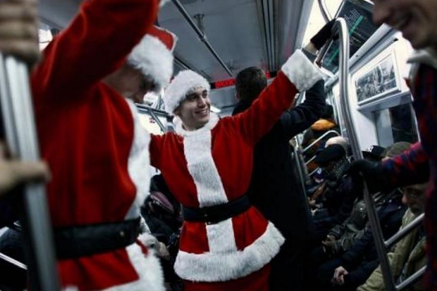Revellers dressed as Santa Claus ride the subway during SantaCon in New York, on Dec 14, 2013.-- FILE PHOTO: REUTERS