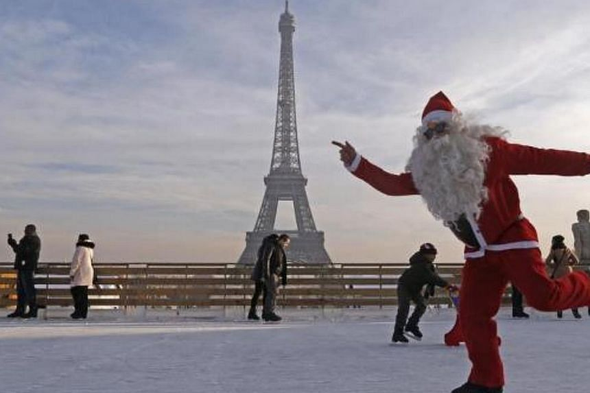 A man dressed as Santa Claus skates on an ice rink across from the Eiffel Tower as part of the Christmas holiday season preparations, in Paris, on Dec 12, 2013.-- FILE PHOTO: REUTERS