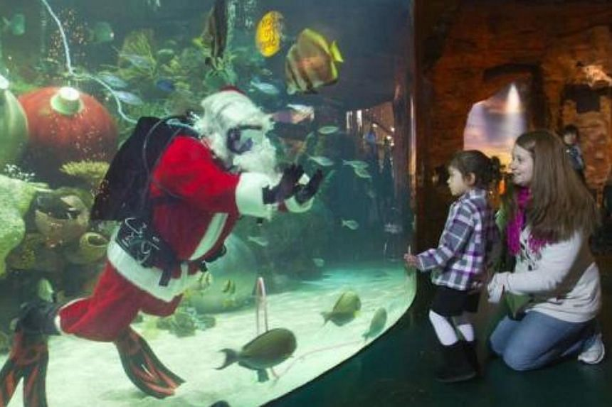 Alexis Libaste, 3, of Henderson, Nevada, looks at Santa Claus with her mother Ashley Libaste at the Silverton Casino Hotel in Las Vegas, Nevada, on Dec 8, 2013.-- FILE PHOTO: REUTERS