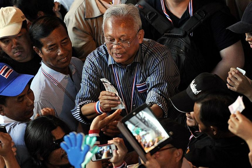Thai protest leader Suthep Thaugsuban (C) receives bank notes from supporters as anti-government protesters march through the streets of Bangkok as part of their ongoing rally on December 20, 2013. -- PHOTO: AFP