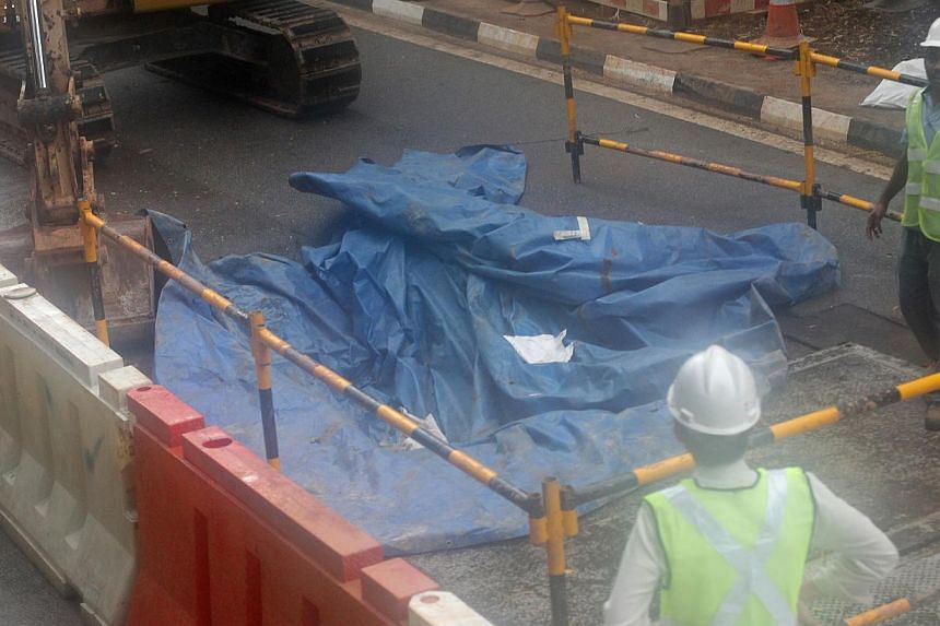 Large hole in the road covered by canvas at Commonwealth Avenue West near Dover MRT Station in the direction towards Buona Vista. -- ST PHOTO: ONG WEE JIN