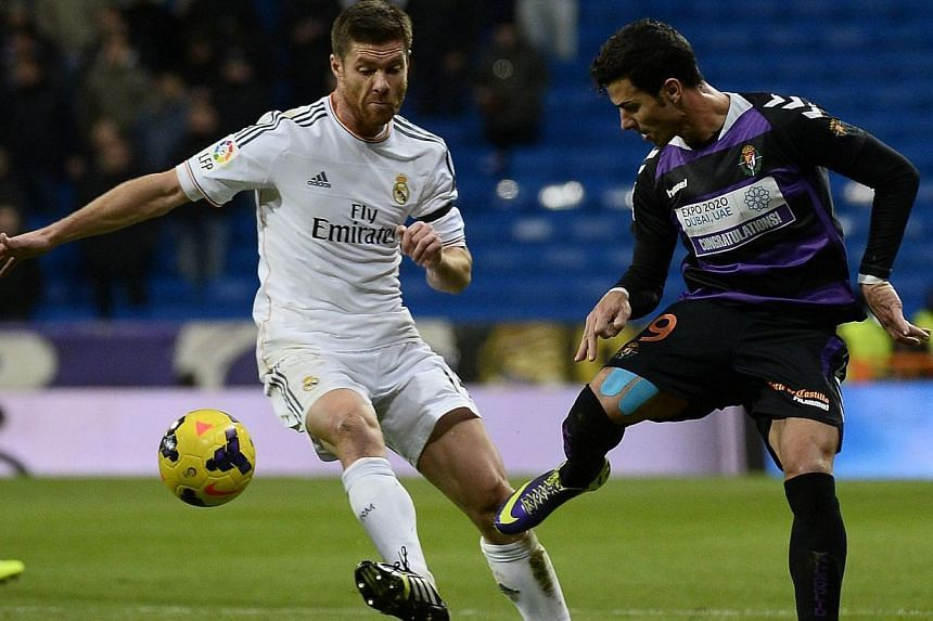 Real Madrid's midfielder Xabi Alonso (left), vies with Valladolid's forward Javi Guerra during the Spanish league football match Real Madrid CF vs Real Valladolid CF, at the Santiago Bernabeu stadium in Madrid, on Nov 30, 2013. Alonso suffered