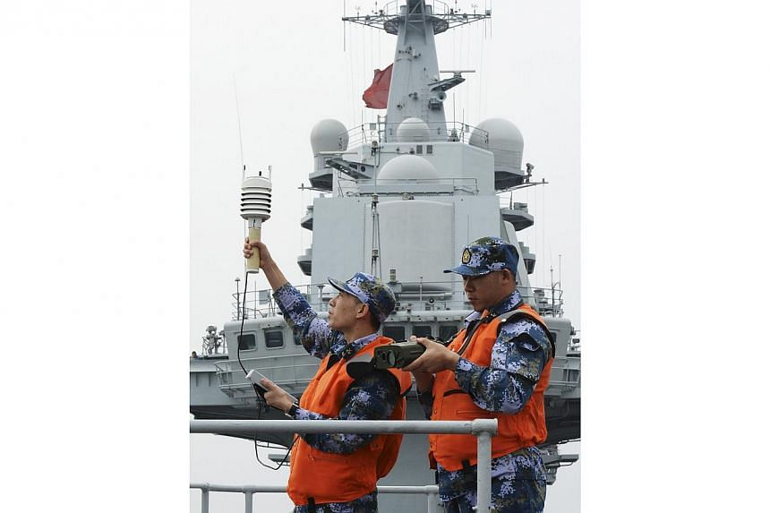 Chinese naval soldiers monitor meteorological indicators on the aircraft carrier Liaoning, as they carry out training in South China Sea on Sunday, Dec 22, 2013.China's first and only aircraft carrier has successfully carried out a series of te