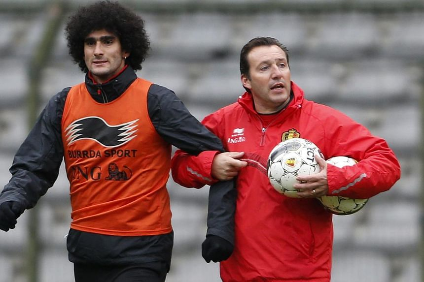 Belgium's football team coach Marc Wilmots gives instructions next to player Marouane Fellaini (left) during a training session at the King Baudouin stadium on Nov 12, 2013. Manchester United midfielder Fellaini could be out until February after