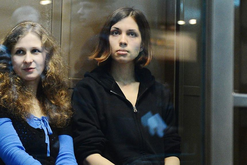 Two jailed members of the all-girl punk band Pussy Riot, Maria Alyokhina (left) and Nadezhda Tolokonnikova, sit in a glass-walled cage in a court in Moscow on Oct 10, 2012.Tolokonnikova was freed from prison on Monday, Dec 23, 2013, under an am
