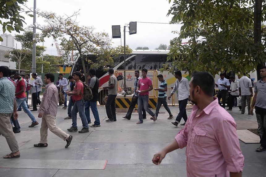 Foreign workers get off shuttle buses at Tekka lane on Sunday, Dec 22, 2013. Human rights group Maruah had misrepresented the nature of a forum meant to discuss foreign worker rights to the owner of a venue they intended to rent, the police said