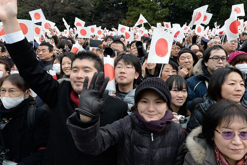 People wave their hands and national flags to celebrate the birthday of Japanese Emperor Akihito at the Imperial Palace in Tokyo on Monday, Dec 23, 2013. -- PHOTO: AFP