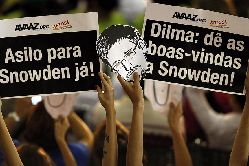 People hold placards and a mask depicting Edward Snowden while Brazilian President Dilma Roussef attends a Christmas ceremony with pickers of recyclable material and homeless people, in Sao Paulo on Dec 19, 2013. Intelligence leaker Edward Snowd