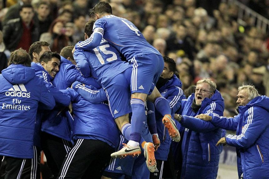 Real Madrid players celebrate after they scored against Valencia during their Spanish first division soccer match at the Mestalla stadium in Valencia on Dec 22, 2013. Real Madrid shrugged off the loss of the injured Gareth Bale as they beat Vale