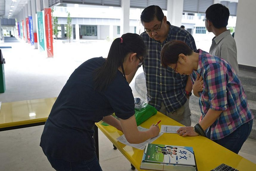It was a bustle of activity yesterday as parents helped to buy books for their children (above) while students were fitted for their new uniforms. -- ST PHOTO: KUA CHEE SIONG