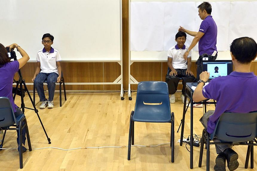 Spectra Secondary students getting their photos taken yesterday. The pioneer batch of 200 students turned up at the school yesterday to prepare themselves for the start of the new year of school.  Spectra Secondary School, located in Woodlands (above