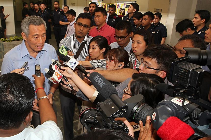 Prime Minister Lee Hsien Loong is surrounded by the media on Tuesday, Dec 24, 2013, after he heard first hand from 38 Home Team officers who were the first responders in the Dec 8 Little India riot. --ST PHOTO:LAU FOOK KONG