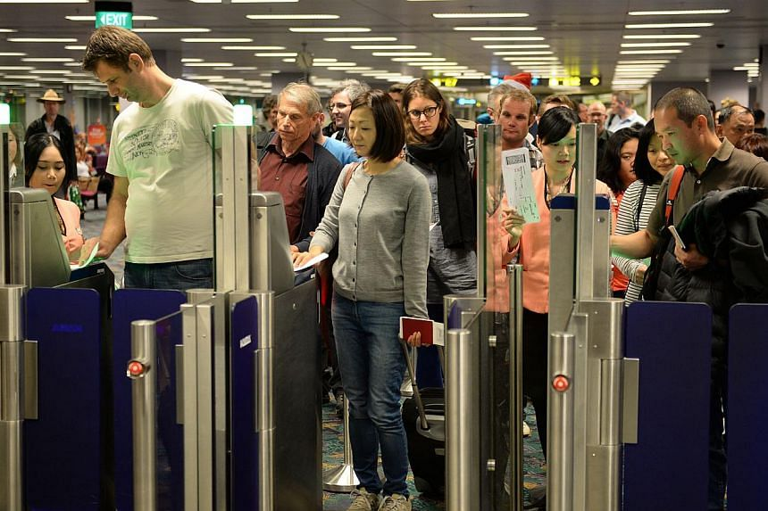 Passengers scan their boarding passes at Changi Airport's new self-boarding gates at Terminal 2 on Monday, Dec 23, 2013. -- ST PHOTO: RAJ NADARAJAN