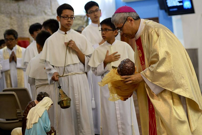 Archbishop William Goh of the Catholic Church laying a figure of baby Jesus during a nativity scene at St Anne's Church in Sengkang. He delivered a Christmas homily at a Christmas mass there, his first as the new leader of the Catholic Churchon