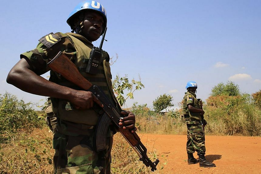 United Nations Mission in Sudan (UNAMIS) personnel guarding South Sudanese people displaced by recent fighting in Jabel, on the outskirts of capital Juba on Dec 23, 2013. South Sudan's army was poised for a major offensive against rebel forces,