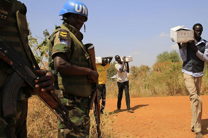 Men carrying boxes walk past United Nations Mission in Sudan (UNAMIS) personnel who are guarding people displaced by recent fighting, in Jabel, on the outskirts of capital Juba on Dec 23, 2013.The United States (US) military on Monday deployed