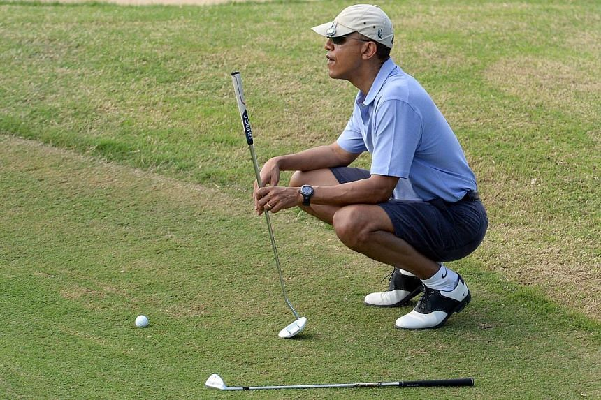 US President Barack Obama playing golf at Mid-Pacific Country Club in Kailua, Hawaii, on Monday Dec 23, 2013. Mr Obama has symbolically signed up for health insurance to promote his own controversial health-care reform legislation while on holid