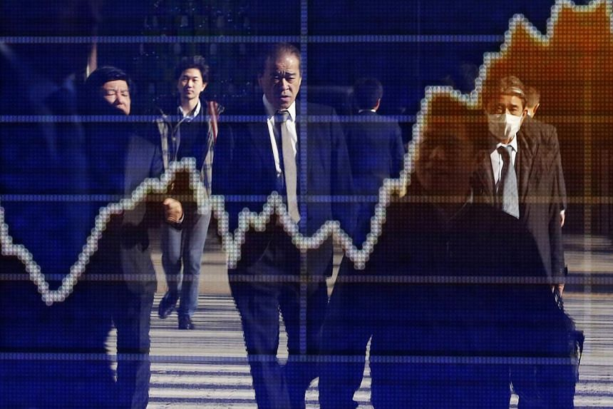 Pedestrians are reflected in an electronic board showing a graph of recent fluctuations of Japan's Nikkei average outside a brokerage in Tokyo on Dec 12, 2013.Japan approved its biggest ever budget on Tuesday, as an improving economy and a sale