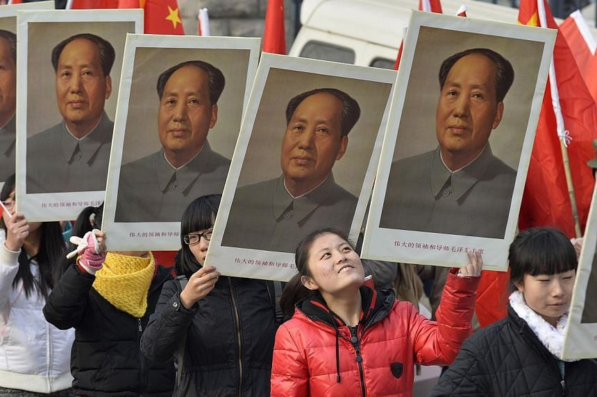 Students hold portraits of China's late Chairman Mao Zedong during a commemorative event ahead of December 26, which marks the 120th anniversary of Mao's birth, at a university campus in Taiyuan, Shanxi province, on Dec 21, 2013. More than 85 per cen
