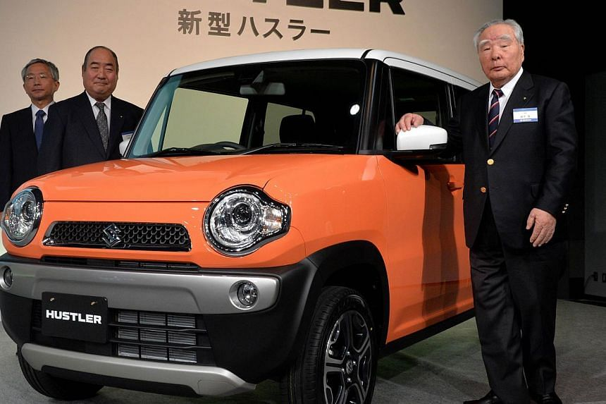 President of Japan's auto maker Suzuki Motor, Osamu Suzuki (right), poses as he introduces the company's new mini sports ulility vehicle (SUV) called Hustler at a press conference in Tokyo on Dec 24, 2013. -- PHOTO: AFP