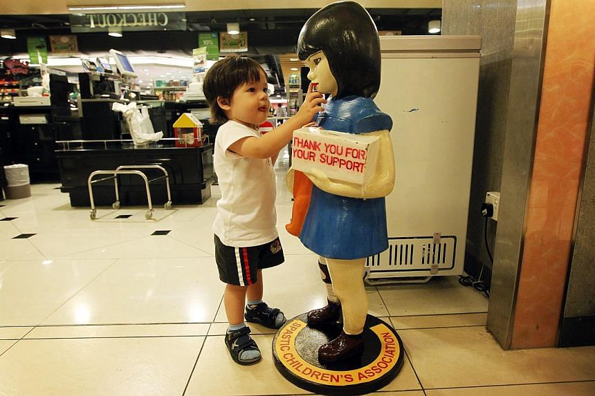 (From left) The Cerebral Palsy Alliance Singapore's new Suzy Doll sports a more cheery face than the old one, dressed in blue. The SPCA introduced its new house-shaped donation box two years ago, to suit counter-tops at supermarket chains.