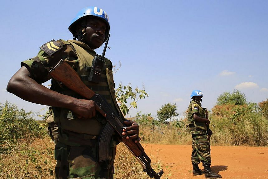 United Nations Mission in Sudan (UNAMIS) personnel guard South Sudanese people displaced by recent fighting in Jabel, on the outskirts of capital Juba on Dec 23, 2013.Thousands of South Sudanese have been killed in over a week of violence with