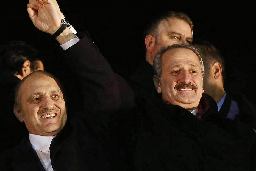 Turkey's Economy Minister Zafer Caglayan and Environment Minister Erdogan Bayraktar (left) salute supporters upon their arrival at the Esenboga Airport in Ankara on Tuesday, Dec 24, 2013.Turkey's environment minister stepped down on Wednesday,