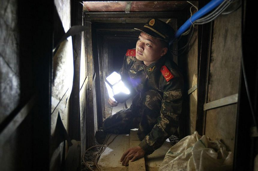A policeman inspects a tunnel which was built by smugglers near the border of Hong Kong, in Changling village of Shenzhen, Guangdong province on Tuesday, Dec 24, 2013. -- PHOTO: REUTERS