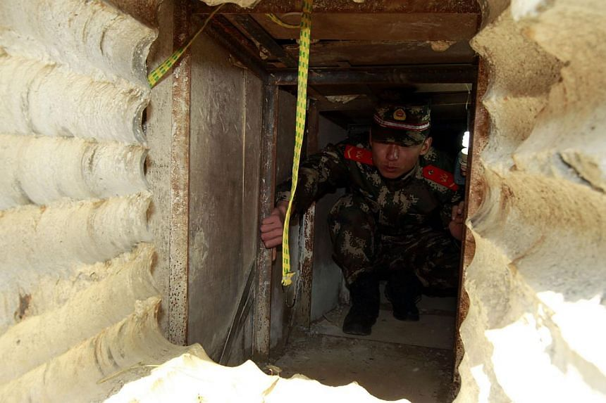 This picture taken on Tuesday, Dec 24, 2013, shows a soldier checking an underground tunnel leading to Hong Kong from Shenzhen, south China's Guangdong province. -- PHOTO: AFP