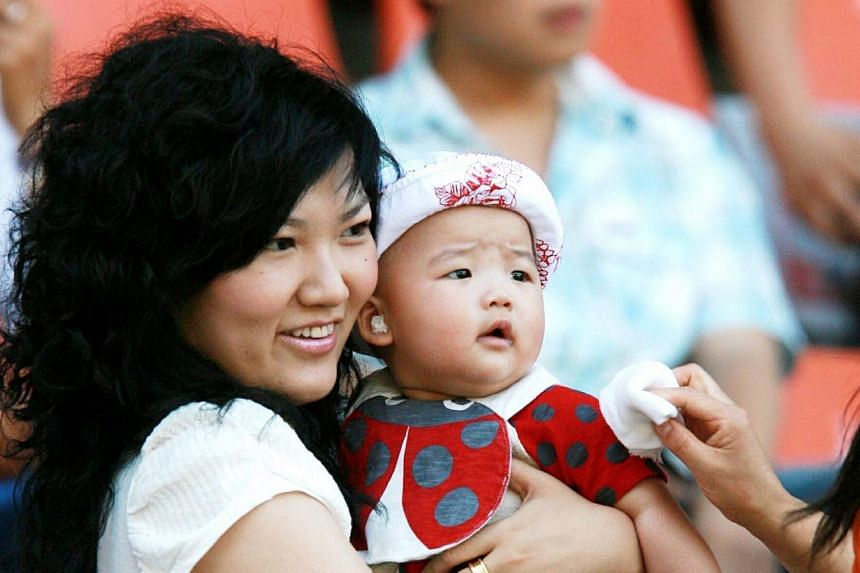 This picture taken on June 16, 2013, shows Wang Ti holding her daughter during a football match in Dalian, north-east China's Liaoning province. Wanghas been sentenced to life in jail for defrauding other star athletes and celebrities of nearly