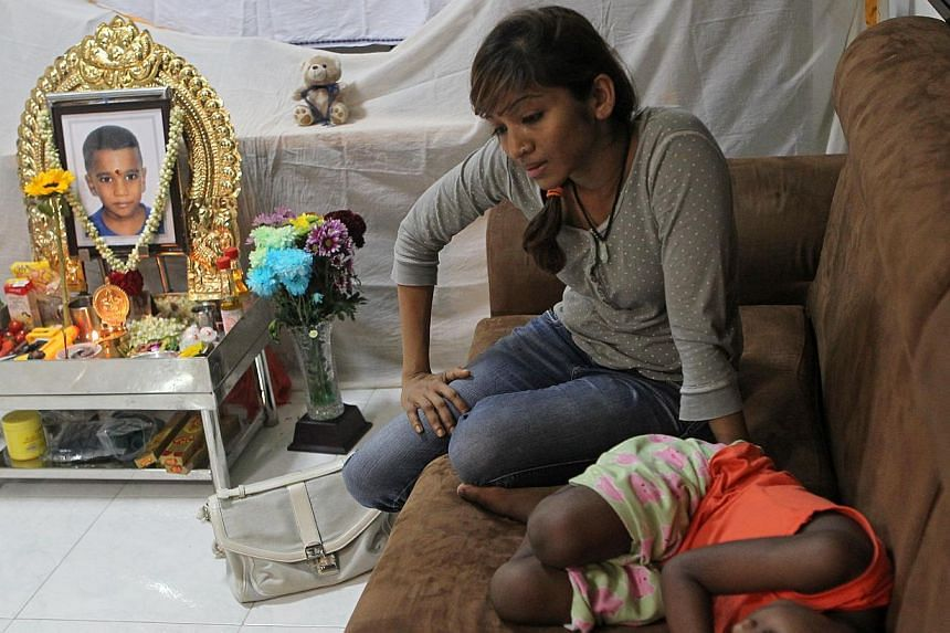 Ms Jaiyesthri Ramasamy (centre) recounts the accidentas her older son,Arshavin Nirmal Kumar,sleeps on the sofa next to his brother's altar in the family's flat. -- ST PHOTO:SEAH KWANG PENG