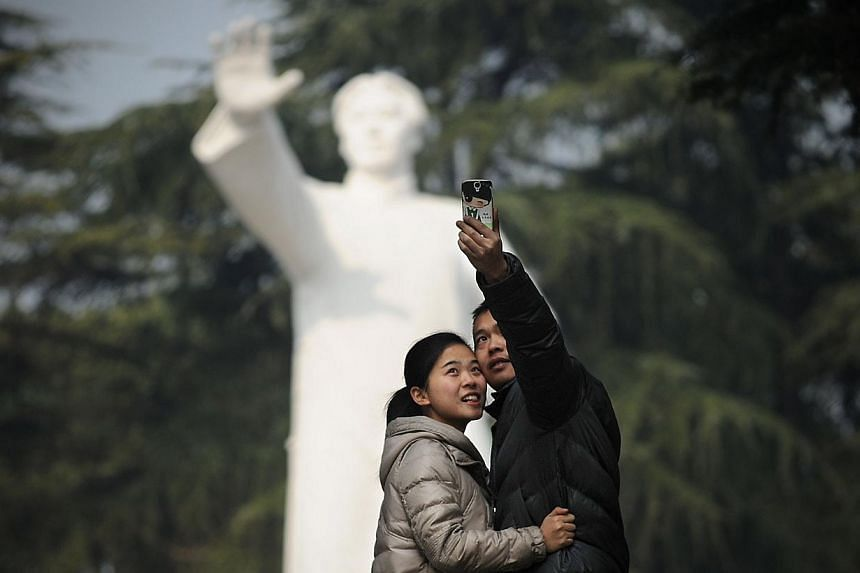 A couple take a photo in front of a statue of former Chinese leader Mao Zedong at a park in Shaoshan, in China's central province of Hunan on Wednesday, Dec 25, 2013. -- PHOTO: AFP
